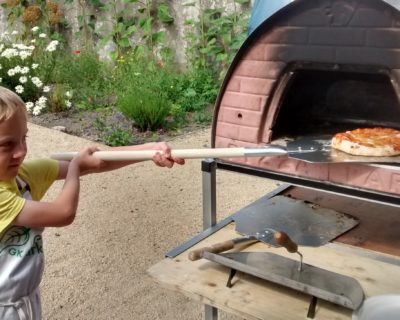 boy putting pizza into wood oven